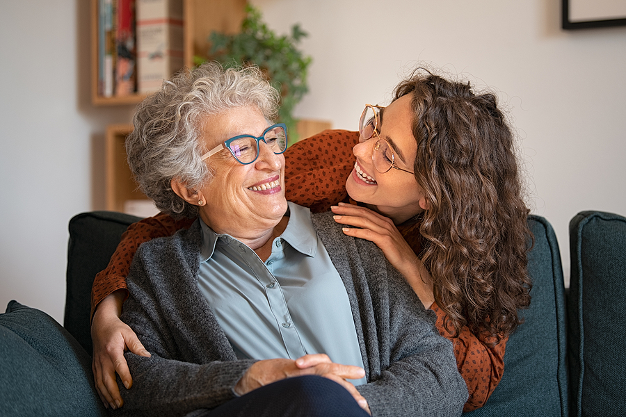 Older woman and adult child hugging at home senior living shuffle